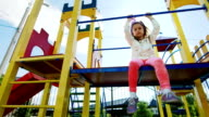 Girl six years old to laugh, have fun and looking at the camera. Sitting on the attraction on the playground video