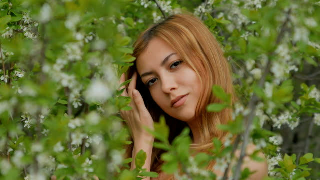 girl smiling and posing among blossoming plum video
