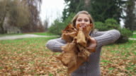 Girl smiling and throwing autumn leaves towards the camera video