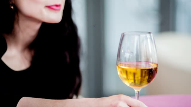 Girl smiling with a glass of white wine video