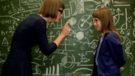 Girl solving math problem on blackboard, looking at teacher for assistance video