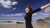 Girl spinning on a sandy beach, looking at the sky video
