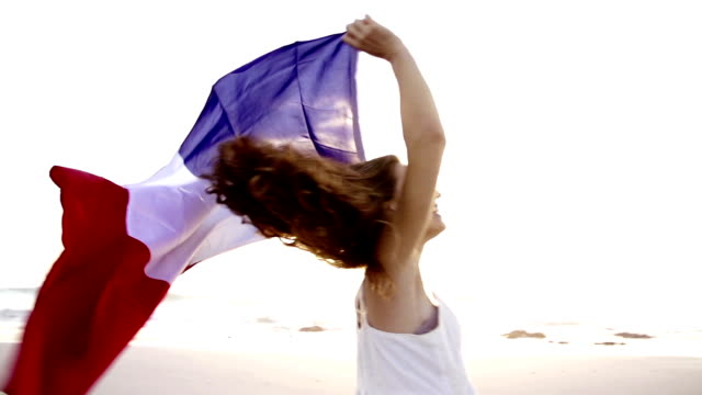 Girl spinning with french tricolore flag in slow motion video