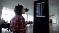 Girl standing in the airport and expects ads about landing on the board of the aircraft. Brunette considering the scoreboard with a schedule of airplanes, looks at his watch and using her smartphone video