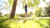 Girl standing on swing under large tree in sunlit field video