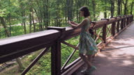 A girl stands at the rail on the bridgework in the park and writing mail video