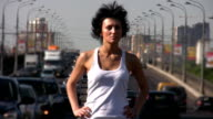 Girl stands on highway middle, moving cars in background video