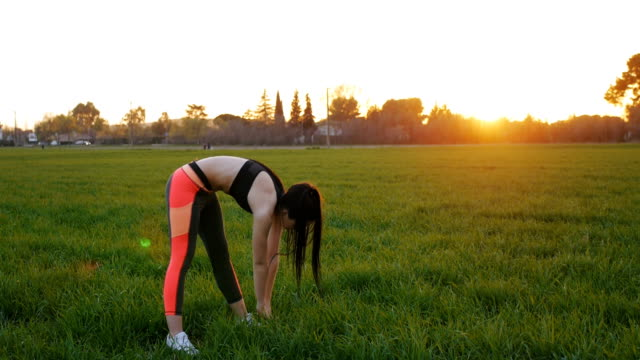 Girl stretching doing standing forward bend outdoors video