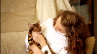 Girl stroking and playing with Bengal cat. video