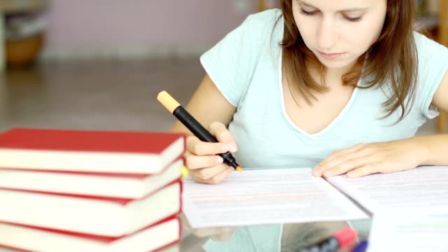 Girl studying and smiling into the camera video
