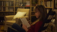 Girl studying literature on chair at home video