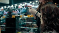 A girl stylist talking of evening make-up in the boutique of women's clothing. video