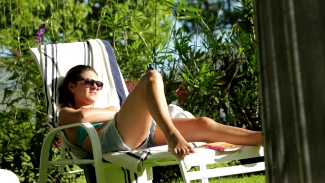 Girl sunbathing by the pool. Candid shot of young woman enjoying the sun by the poolside video
