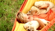girl swinging in hammock with puppies video