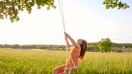 SLO MO Girl swinging in the meadow video