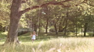 SLO MO DS Girl swinging under a big tree video
