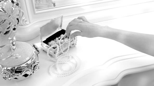 girl takes a pearl necklace. He is sitting near a mirror. chic luxury interior video