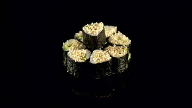 Girl takes chopsticks sushi on a black background. video