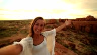 Girl takes selfie portrait with spectacular landscape at sunrise video