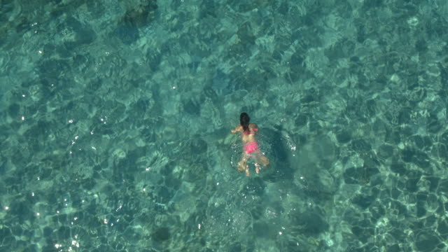 AERIAL: Girl taking deep breath, submerging, swimming in transparent ocean water video