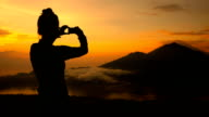 Girl taking pictures of sunrise over Lake Batur, Volcano Agung and Abang, Bali video