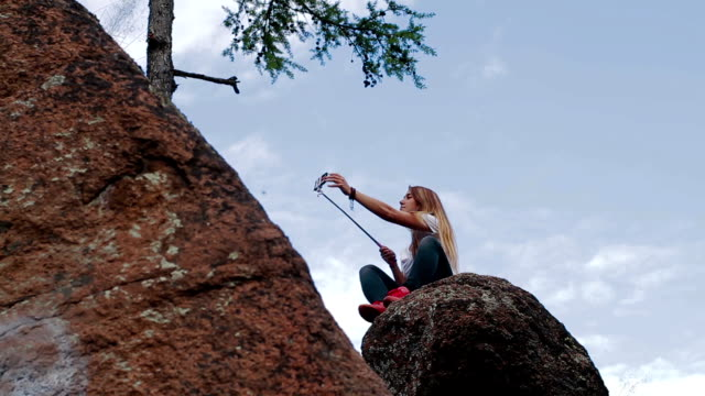 Girl taking selfie using smartphone in mountains video