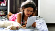girl teen playing tablet game internet sitting on bed next to cat video