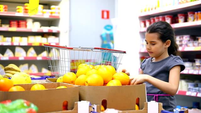girl teen with in supermarket to buy fruit orange video