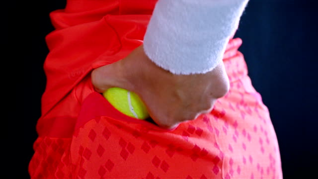 Girl tennis player taking a tennis ball from her rock pocket and preparing for service, black background video