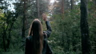 Girl throwing arms in Autumn in slow motion, smiling into the camera. Fashion pose in forest, smiling attractive brunette on a walk video