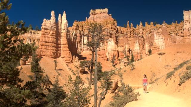 Girl tourist walking along the trail, visiting sunny Bryce Canyon landmark video