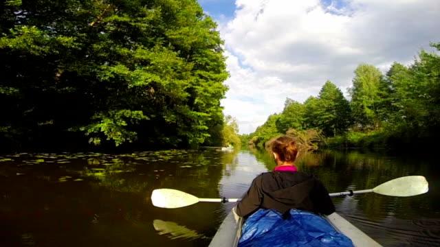Girl traveler sitting in kayak, resting. Wide river, slow motion video