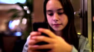 Girl uses a smart phone in coffee shop video