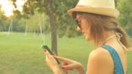 Girl using cellphone outdoors. video