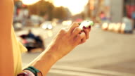 Girl using cellphone with de-focused city traffic. video