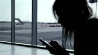 Girl using smart phone at airport terminal, waiting for flight video
