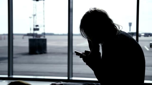Girl using smart phone at airport terminal, waiting for flight video
