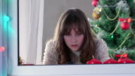 Girl using smart phone near Christmas tree something typing video