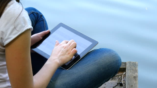 Girl using tablet pc and relaxes by the lake sitting on the edge of a wooden jetty near the water surface on summer evening. Woman browsing photos, using app and communicating outdoors. video