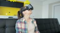 Girl using virtual reality at home. video