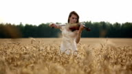 Girl violinist playing the violin wheat field video