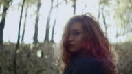 Girl walking and rounding in sunlight in forest video