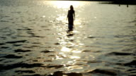 girl walking in from the sea at sunset video