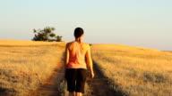 Girl walking on empty rural road far away video