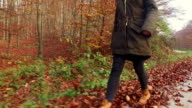 Girl walking through leaves.  Slow motion video