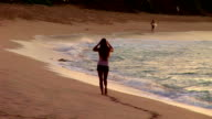 Girl walking up beach video