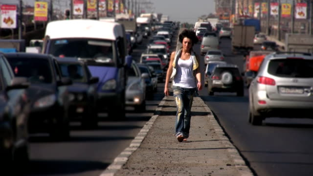 Girl walks to camera on highway middle in city video