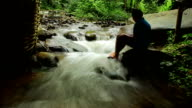 Girl washing their feet in the stream video