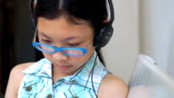 Girl watching  movie or cartoon in digital tablets with headset video