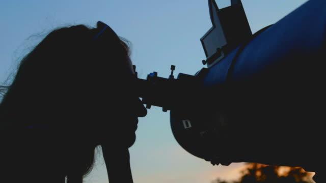Girl watching stars through a telescope outdoors. video